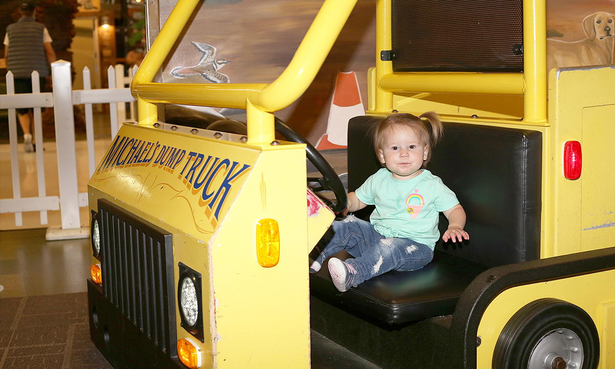 Little girl playing in the dump truck in the Build It gallery