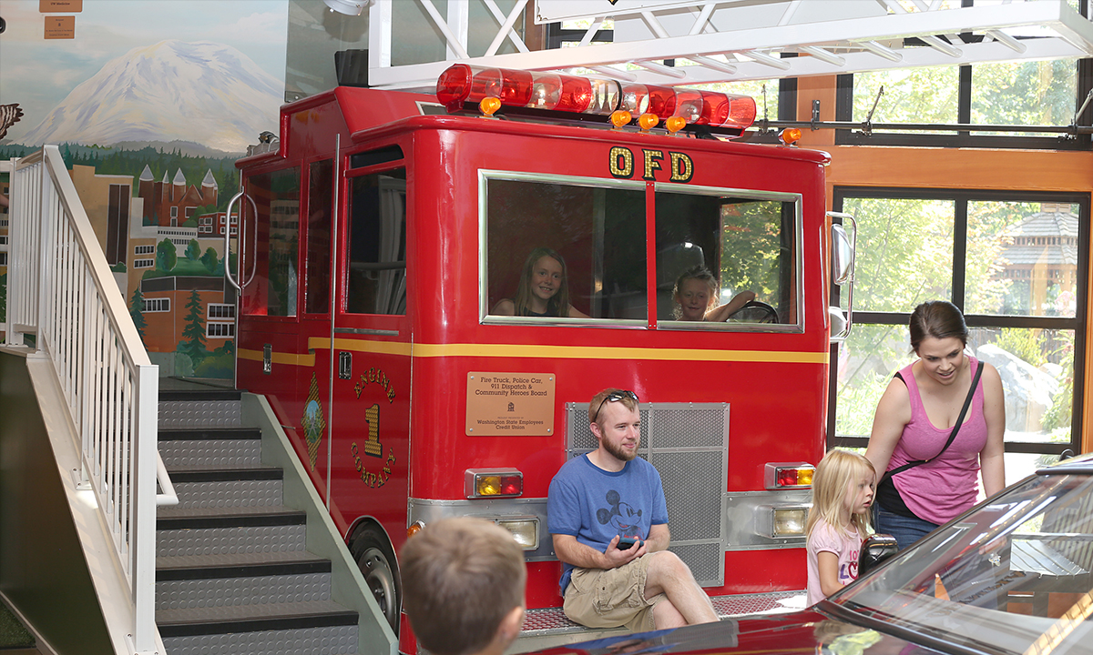 Family exploring the firetruck and police car int he Emergency gallery