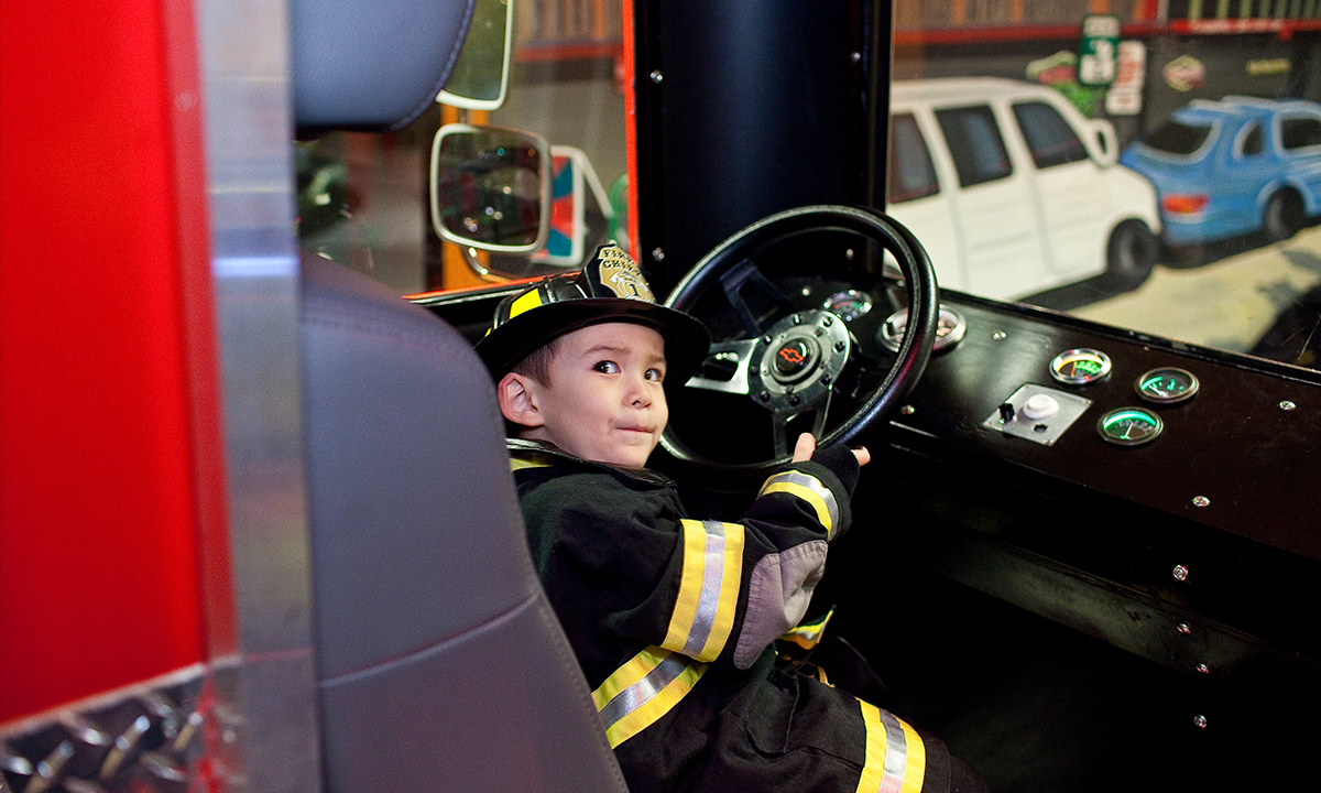 Boy dressed as firefighter in the firetruck