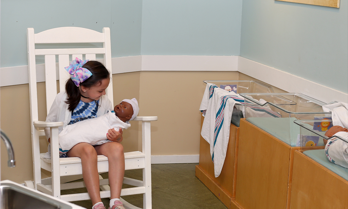 Girl holding a baby doll in the Nursery