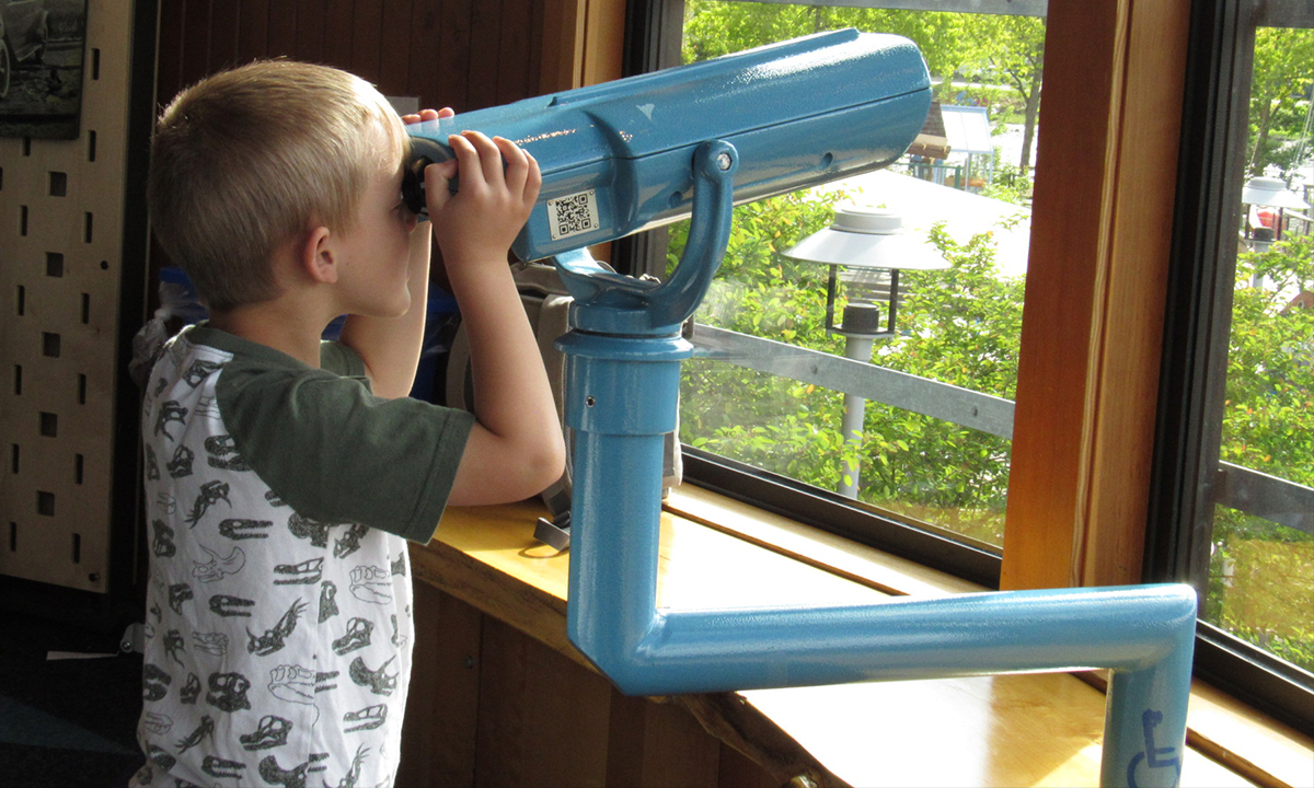 Boy looking out to the ODC with the binoculars