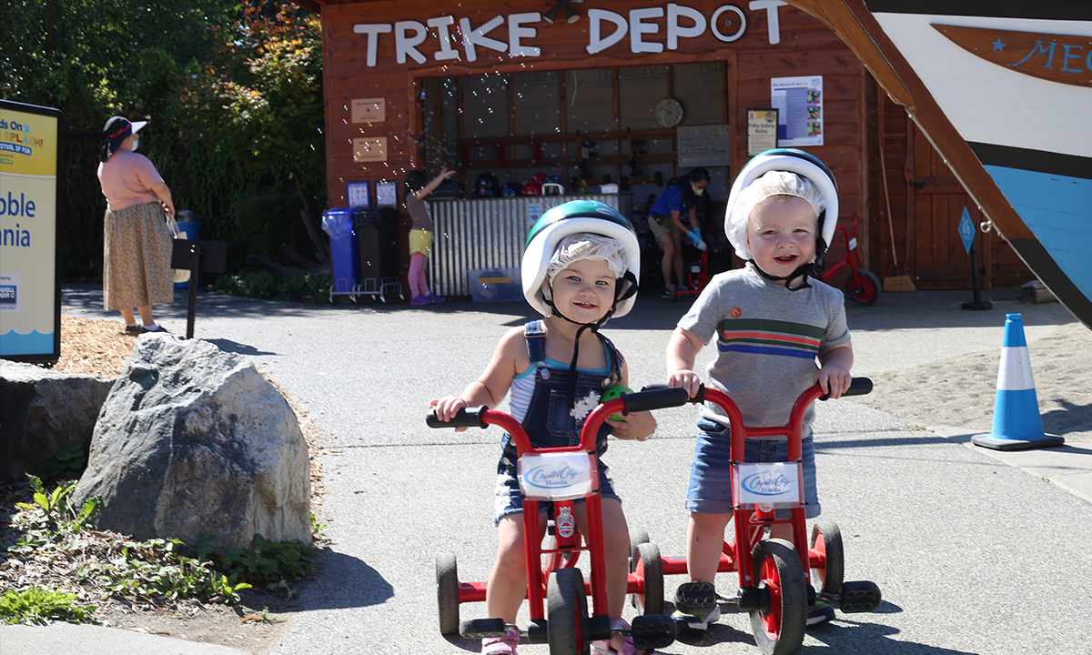 Two kids riding tricycles in front of the Trike Depot