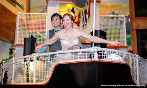 Bride and groom making Titanic pose on the bow of the cargo ship