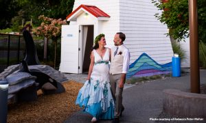 Bride and groom walking along the Trike Loop path in front of the Lighthouse and Orca sculpture